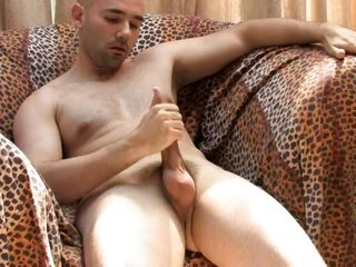 pretty man with a smooth-faced slavemaster seizes his cock stiff on a couch
